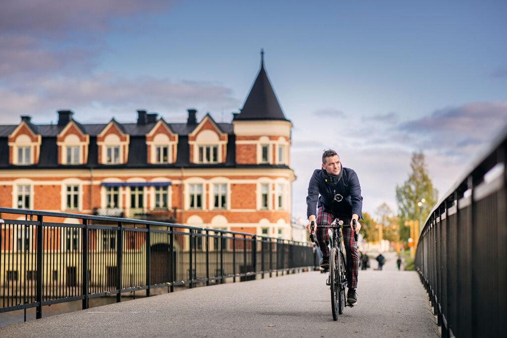 Cyklist cyklar i gryningen över bro i Eskilstuna.