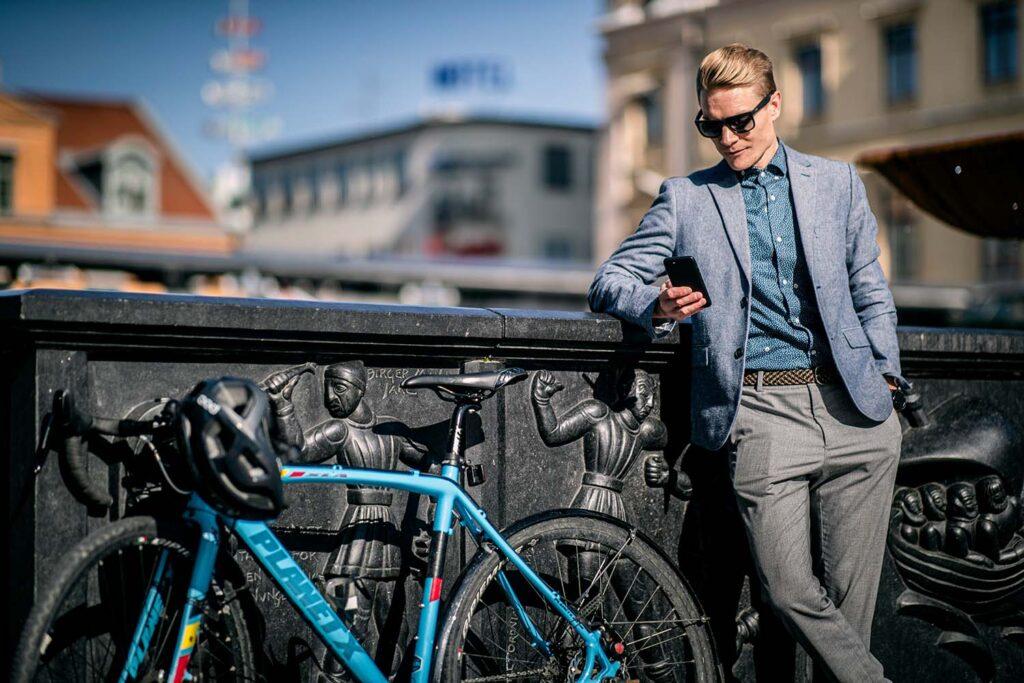Man står och läser i sin mobil bredvid sin cykel.