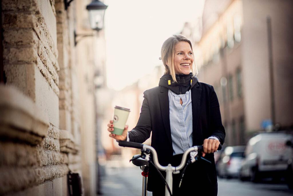Cyklist som tar en paus med en kaffemugg i handen.