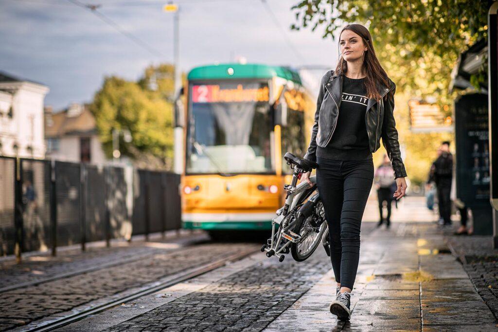 Kvinna går med sin vikcykel vid Norrköpings station.