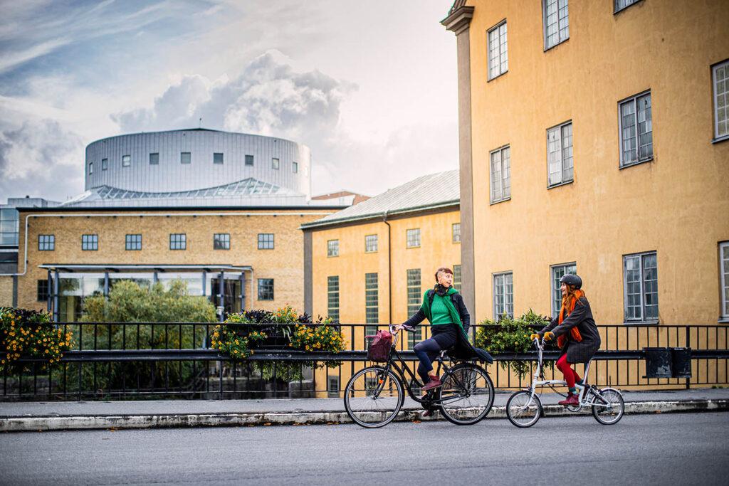 Två cyklister i Norrköping som cyklar över bron vid konserthuset.