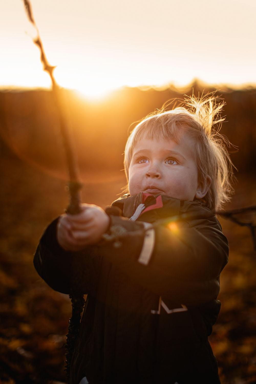 Liten pojke håller upp en pinne med solen som strålar bakom sig.